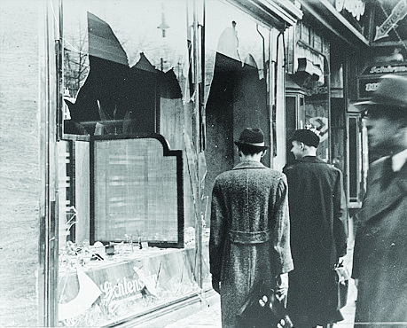 "<p>Photo: USHMM, courtesy of National Archives and Records Administration, College Park Germans pass by the broken shop window of a Jewish-owned business that was destroyed during Kristallnacht in Berlin, Germany. The ""Night of Broken Glass"" was a planned series of acts of violence against Jews throughout Germany, Nov. 10, 1938.</p>"
